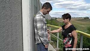 Mature woman over 60 gives a blowjob to hot young bloke outdoor